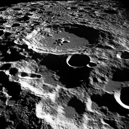 """Daedalus Creator Print - Apollo 11 (16-24 July 1969) --- An oblique of the Crater Daedalus on the lunar farside as seen from the Apollo 11 spacecraft in lunar orbit. The view looks southwest. Daedalus (formerly referred to as I.A.U. Crater No. 308) is located at 179 degrees east longitude and 5.5 degrees south latitude. Daedalus has a diameter of about 50 statute miles. This is a typical scene showing the rugged terrain on the farside of the moon. While astronauts Neil A. Armstrong, commander, and Edwin E. Aldrin Jr., lunar module pilot, descended in the Lunar Module (LM) """"Eagle"""" to explore the Sea of Tranquility region of the moon, astronaut Michael Collins, command module pilot, remained with the Command and Service Modules (CSM) """"Columbia"""" in lunar orbit."""