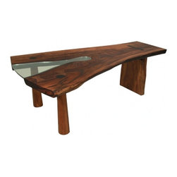 ecofirstart - Solid slab Tamboril dining table - Feast your eyes on this handcrafted beauty. The artist sources South American hardwood from trees that have long ago fallen or been felled, then uses a sizeable slab to create this beautiful and unique dining table. Glass is inset in the natural tree angle, and it sits on three wooden legs.