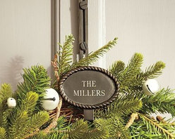 """Rustic Rope Adjustable Door Wreath Hanger, Antique Bronze finish - The natural look of a delicate rope surrounds the name plate of our wreath hanger. Strong and sturdy, it gives your wreath an elegant, personalized look during the holidays. 5"""" wide x 4.5"""" deep x 14-18"""" high (adjustable) Made of iron. Fits over doors up to 2"""" thick. Monogramming is available at an additional charge. Monogram will be centered on the plaque. Catalog / Internet Only."""