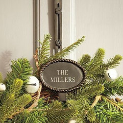 "Rustic Rope Adjustable Door Wreath Hanger, Antique Bronze finish - The natural look of a delicate rope surrounds the name plate of our wreath hanger. Strong and sturdy, it gives your wreath an elegant, personalized look during the holidays. 5"" wide x 4.5"" deep x 14-18"" high (adjustable) Made of iron. Fits over doors up to 2"" thick. Monogramming is available at an additional charge. Monogram will be centered on the plaque. Catalog / Internet Only."