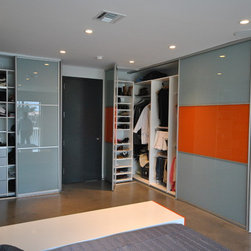 Modern Sliding Closet Doors - Whether installed as part of a larger closet system design or added to existing closet spaces, the right door will pull together an entire room. Beautiful designs combined with the latest in European trends are the hallmark of the most in-demand in Miami sliding closet doors from Armadi. Our sliding doors can do so much more than close in a closet. They can let in light, divide rooms or create a bold showpiece in your home.At Armadi Closets, a development team of interior designers, architects and engineers works together to create sliding closet doors based upon cutting-edge European technology. This innovative European system features unique styling that is suitable for every home and storage location. Using one slim profile, you can create 10 different door designs, making it one of the most customizable bi-fold closet doors in Miami. While traditional closet doors may be simply a basic wood door on a hinge, the doors offered by Armadi Closets can swing, slide or fold to divide rooms and closet space beautifully.No matter how attractive a door may look, it will not enhance your home unless it works properly. Nothing is more frustrating that having a sliding door come off its track each time it is opened. At Armadi Closets, high quality construction is a priority. Durable raw materials that exceed the standards used by our competitors ensure that doors glide effortlessly. Our durable, lasting construction means that your new door will look and work fabulously for years to come.
