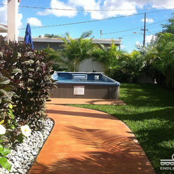 Backyard Endless Pool® Swim Spa - And the path paved in gold tones leads where? To an Endless Pool Swim Spa, of course! The wall of palms provides privacy, a tropical vibe and, when the sun is low, some elegant shadows. That makes a lovely setting for exercise, relaxation, or entertaining in this Endless Pool.
