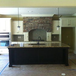 White Painted w/ Beaded Board Doors and Dark Stained Island - This is a painted white kitchen we did with beaded board doors that featured two small cabinets on each side of the cooktop that were the base for a beautiful stone covered arch. The island is stained a dark stain and has bookcase ends on each end.