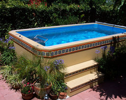 Original Endless Pools®, Patio Pool - Finished in adobe yellow with ornamental tile, this Endless Pool demonstrates what an attractive showpiece an above-ground pool can be!  The container garden and lush hedging complete the Santa Fe vibe.