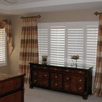 Swags - Silk swag and asymmetrical cascades, and stationary draperies slightly breaking at the floor installed over shutters on short decorative wood poles with rings.