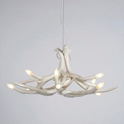 "Superordinate Antler Pendant - Described by Brooklyn-based designer Jason Miller as ""nature made better,"" the Superordinate Antler Collection (2003) could be called an artful collision between hunting lodge décor and high-end contemporary design. Made completely out of ceramic with classic flame light bulbs at its tips, it will certainly provide a bright conversation piece for your next dinner party. When turned on, the bulbs throw shadows of the branch-like antlers onto the walls and ceiling, creating further decorative forms."