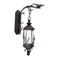 Birds and Branches Decorative Wall Mounted Hanging Lantern - This wall mounted lantern adds a decorative accent to your home, porch, or patio. The hanger measures 16 1/2 inches tall, 7 inches wide, 14 1/4 inches deep and mounts to the wall with a single nail or screw. The lantern is 19 1/2 inches tall, 6 inches in diameter, and hangs 3 1/2 inches from the hook on the wall bracket. The glass globe measures 8 inches tall and approximately 4 1/2 inches in diameter. This piece has a wonderful weathered, antique finish, and looks great with a flickering LED candle in it.