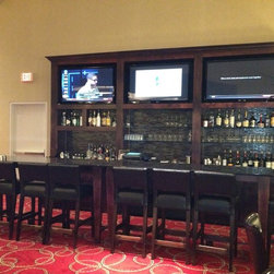 Custom Bar and Tables - Media area with shelving to accommodate alcohol for a bar and cafe area at a Metairie, LA Hotel. The bar and cafe tables were made from solid cherry. The area behind the bottles has glass tile installed along the back and is back-lit to show the tiles at night.A black granite top was installed on both the bar area and the media area.