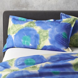 """Marimekko Kehakukka Blue King Sham - Periwinkle blossoms and dappled green leaves bloom rich, watercolor hues in Aino-Maija Metsola's exquisite design inspired by the marigold (""""kehakukka"""" in Finnish) and printed on soft, 100% cotton. Pillow shams are randomly cut, resulting in a different pattern sampling to each one. Shams have overlapping flap closures. Bed pillows also available."""