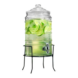 Home Essentials - Cylinder Ribbed Glass Beverage Dispenser on Iron Rack - Dispense your favorite tasty beverages in style using our clear glass drink dispenser on wrought iron rack. Fill this gorgeous beverage dispenser with ice cold water or bright pink lemonade for a chic, modern addition to any celebration! Constructed from thick, high quality glass, this beverage essential will hydrate guests and keep the host at ease for years to come. Our beautiful, classic-looking beverage dispenser looks great on your patio, kitchen counter and anywhere else you want to use it. The metal stand conveniently elevates jar for an attractive presentation and easy dispensing indoors or out.   * Capacity: 1.5 gallons