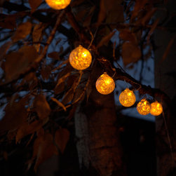 "Allsop Aurora String Lights Clear with Amber - Illuminate your outdoor spaces with beautiful and festive Aurora String Lights Clear with Amber. These stunning clear glass gems are handblown into gorgeous globes to decorate your yard, path, or deck. Six globes accented with amber luminescent details adorn a clear wire and come complete with six high-powered LED lights and copper hanging hooks. Aurora String Lights are powered by the sun, with a solar panel located up to 15 feet away from the first glass globe. Plant or mount the solar collector away from the lights and enjoy the glow at night while collecting the maximum amount of sunlight during the day. Each piece is a handcrafted work of art, and no two globes are exactly alike. Enjoy the beauty of their artisan nature The hand-crafted Aurora Glow string lights are beautiful wrapped amidst the greenery of an arbor, archway, tree or deck railing. Perfect for an outdoor room or beneath an umbrella Equipped with a photo light sensor, the lights will turn themselves on at dusk and off at dawn. Totally sustainable, hang these stunning string lights once and enjoy their artisan glow every night  Aurora String Lights come equipped with 6 copper hanging hooks, a 5x5 solar panel to power the included rechargeable battery.  Dimensions: Six 2.5 globes spread 22"" apart with the solar panel up to 15' away. Total string length is 25'."
