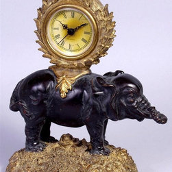 AA Importing - Elephant Tabletop Clock - Carefully crafted from durable resin, this tabletop clock has a detailed elephant design and stately appearance. Gold-tone frame has scrolled accents throughout. Easy to read clock has faded yellow dial and black Roman numeral indicators. Decorative piece also works well on display shelves. Elephant design. Resin.  Battery operated (not included). 6 in. L x 4 in. W x 9.5 in. H