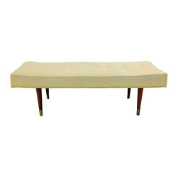 Pre-owned Classic Mid-Century Long Low Profile Bench Ottoman - A circa 1960 Mid-Century Modern long low profile upholstered bench in original cream naugahyde. The bench features tapered wood legs with brass feet caps and a tufted seat. It would be great for the end of a bed or on the other side of a coffee table for additional seating.
