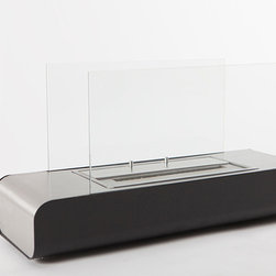 """EcoPyro TG-01 Donner Freestanding Ventless Ethanol Fireplace 23 5/8"""", Chimney Bl - Donner was fabricated with the sole purpose of providing an impressive scale of flame. The result of a large burner source designed into a sleek, understated windswept lower body with upward extending glass panels. Sitting on 4 short leg floor protectors, Donner exemplifies modern free standing fireplaces designed around a low profile. The solid body of Donner raises a mere 4 inches from the floor. The glass extends from the body to reach the fireplace full height of nearly 8″. Conceptualized with glass panels as sides, when ignited, the flames can be viewed from any angle in the room. The top of the base features a single sheet of decorative stainless steel which slopes down on the ends transforming into the sides of the fireplace. Donners streamlined low profile body and large 1.5 liter burner source bring full attention to the fire."""