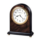 "Howard Miller - Walnut Finished Wood Mantel Clock with Inlaid - This elegant, highly attractive clock is made to give a fashionable, stylish feel to any room. The beautiful, dark color is given by a walnut piano finish, with wood burl patterns that give the piece a subtle texture. The clock is accented with a brass finish. * An attractive high-gloss walnut piano finish on a hardwood arch table clock featuring a wood burl pattern on the front and back, with black sides and base.. Polished brass button feet. . Polished brass tone waterfall bezel and glass crystal. The off-white dial offers black Arabic numerals, black hour and minute hands, with a brass second hand. . Quartz movement includes battery. . H. 6-1/2"" (17 cm). W. 5-1/4"" (13 cm). D. 2"" (5 cm)"
