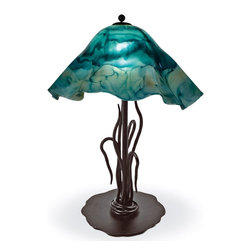Mathews & Company - Wrought Iron River Reed Table Lamp with Large Glass Shade - This lovely and unique lamp is a wrought iron masterpiece. With strand after strand of iron bundled together at the bottom - which sits on a sturdy circular base - they stand upward resembling reed vines climbing and bending with the wind. Created by the artisans at Matthews & Company, this beautiful lamp is topped off with a hand blown-Large Glass Shade this is narrow in shape with lovely hanging scalloped edges, blown in hues of warm amber, gold, and brown. This design will reflect warmth and light and lend a welcoming, relaxing air to any home.Pictured in Turquoise shade and Black finish.