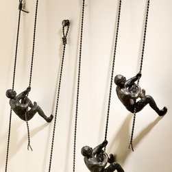 Climbing Man - Wall Mounted - Diminutive coils in wire convey the taut tension of the ropes grasped by the Climbing Man, a wall sculpture with a strong understanding of human figure portrayed in tense, stilled motion. Practical in its proportions and ideal for narrow accent walls, this symbolic piece adds dimension to flat planes and speaks to a optimistic, work-oriented take on daily life.