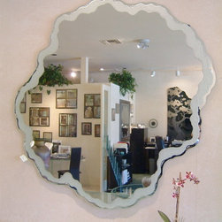 "Seafoam Border Decorative Mirror - ART THAT REFLECTS...... Decorative mirrors with frosted, etched and carved designs by Sans Soucie Art Glass add a beautiful custom element to any bathroom mirror, or as a glass wall art piece or decorative bathroom mirrors.  There's no limit to design, shape or size, and mirrors can be sandblast etched or carved on the front or back surface, depending on the desired effect.  A very popular mirror effect is our overlay effect.   Sans Soucie hand chisels the mirror edges to create stunning freeform shapes to be incorporated as a design element, or an overall freeform shape.   Far more custom than any ordinary frame, Sans Soucie creates beveled mirror strips that can be applied to your existing mirror!  Any conceivable design, texture or pattern is sandblast frosted, etched and carved into the mirror surface.  Designs can also feature airbrushed color.  Mirrors can be backlit for bathroom vanities.   Glass wall art pieces are perfect for areas such as over a fireplace mantel, a main entry, or literally anywhere you want to o add a specialized, custom art glass piece.  Included with your mirror will be an invisible ""floating"" hanger.   The mirror will hang safe and secure, and will stand off the wall approx. 1/4"" for a beautiful, free floating effect.Sea Foam Border Mirror - Sans Soucie Art Glass.  This mirror is 60"" dia and is sandblast etched and carved on the front surface with a border that ranges between 2"" to approx. 3-1/2"" wide in our light moonscape texture, forming the look of sea foam.  The mirror has been hand chiseled to form an irregular edge.  Mirrors are hand crafted and are custom made to order, available in any size or shape."