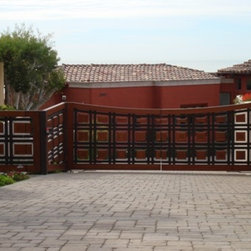 Custom Wood Double Swing Entry Gate with Pedestrian Gate - This gate is made from a steel super structure that has exposed steel and cladding with a Mahogany that has been picture framed and is cabinet grade carpentry. To top this of we have included a pedestrian gate that is concealed and FAAC subterranean gate operators to  give a clean look and function with no problems.