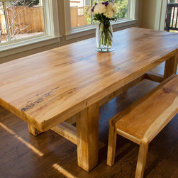 """Chataqua dining table - This dining table is 9' long, 4' wide, and 30"""" tall. It was created from a local maple tree which was planted on a vacant lot in our town back in 1903. Up until 1985 this maple was the """"Tree House Tree"""" on Emma street, and served as the secret hideout for at least 3 generations of children from all over town. One massive slice of the tree trunk including the natural edges has been """"wrapped"""" in matching wood to provide a formal rectangular shape, which still pays homage to the shape of the original tree. The massive character of the extra-thick top is supported by a similarly proportioned base structure, made from the same beetle killed tree."""