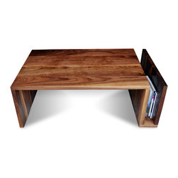 "2131 - Walnut Coffee Table With Sleeve - This walnut coffee table has a minimalist design and just as simple a function. The plane of walnut folds at the leg and returns back up to create a sleeve for storing books or magazines. The piece is made of a solid 1.25"" thick piece of walnut and assembled with clean mitered joints."