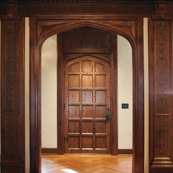 Jacobean Transitional Door - 4-centered arched door with an overframe fastened with clavos, carved spandrels and European hardware.