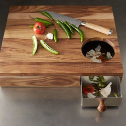 "Storage Cutting Board - This cutting board has enough ""wonderful"" to make a foodie weep joyful tears. That might seem a bit dramatic, but check it out: It has a hole to sweep tomato stems and onion skins into as you chop, and (wait for it) a pull-out drawer for easy emptying. So not only can you cook like a gourmet chef, but you can clean like Martha Stewart too."