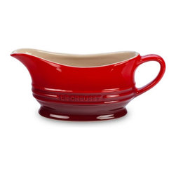 Le Creuset - Le Creuset 12 oz. Gravy Boat - Cherry - PG9700-1267 - Shop for Bowls and Candy Dishes from Hayneedle.com! The cute and classic Le Creuset 12 oz. Gravy Boat Cherry comes equipped with a petite handle and spout perfect for serving gravy and other sauces on your family's dinner table. The warm red finish goes with almost any kitchen decor and the sturdy stoneware construction will serve you for many years. About Le Creuset of America Inc.From its cast iron cookware to its teakettles and mugs Le Creuset is a global standard of inimitable color and quality. Founded in 1925 in the northern French town of Fresnoy-Le-Grand Le Creuset still produces enameled cast iron in its original foundry. Its signature color Flame was modeled after the intense orange hue of molten cast iron within a cauldron (or creuset in French) and has been a Le Creuset bestseller from the company's first year to the present day.Though best known for its vibrantly colored cookware and original inventions such as the Dutch oven Le Creuset has also forged a name as a creator of stoneware mugs and enamel-coated stainless steel teakettles. The style and performance of Le Creuset's Cafe Collection and tea accessories are rooted in classic French cookware: bold colors cylindrical loop handles unmatched thermal resistance and heat distribution and of course the iconic Le Creuset three-ring accent. Through its consistent qualities of authenticity originality and innovation Le Creuset maintains a connection to both heritage and modernity.