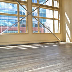 Executive style in Downtown Calgary - Large south windows give this space plenty of sunlight and the warmth of the wood flooring creates a cozy feel in this large space.