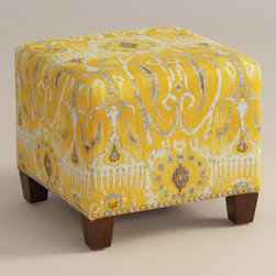 """World Market - Alessandria McKenzie Ottoman - Cozy up with our custom-made Alessandria McKenzie Ottoman, handcrafted in the U.S.A. with cotton upholstery and nail head trim. Showcasing a fanciful ikat motif on a lemon ground, this plush ottoman makes a bold statement. Pair two ottomans for a dramatic """"bench"""" at the foot of the bed. Shop our coordinating bed or headboard in the same custom fabric for a pulled together look."""