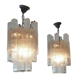 Pre-owned Italian Mid-Century Glass Chandeliers - A Pair - These Italian Mid-Century style chandeliers date back to 1960. The pair of textured clear glass shades are suspended from a two-tiered metal frame. It has been re-wired for the U.S. and is ready for use! They are sure to set a wonderfully elegant ambiance in the foyer or dining room of any design aesthetic.