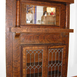 """Oak Bookcase Mantel - Oak bookcase fireplace mantel with the original quarter sawn oak faux finish over clear oak and leaded glass bookcase doors. Faux finish is wearing off of the top of the mantel shelf and the top of the bookcase shelf, but is in remarkably good condition elsewhere. Retains the original beveled glass mirror. 60""""W x 84""""H x 12""""D ca.1900"""