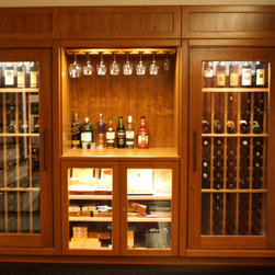 Wine and Cigar Cabinet - The finished basement room in this luxury home in central Massachusetts has custom designed wood paneling. At one end of the room, the staircase leads to the main floor of the residence. Underneath the stairway, there was unused space that was a perfect spot for a small wine closet.  The homeowner was anxious for his small wine cellar, but he had other items on his wish list. Could he also store his cigar collection in the same cabinet?