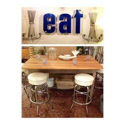 """Form & Function Retail Store Offerings - Vintage """"eat"""" letters, silver modern sconces, and an architect's drafting table that has been converted into a kitchen island."""
