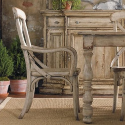 Wakefield X-Back Dining Arm Chairs - Set of 2 - Full of rustic, woodsy charm, the Wakefield X-Back Dining Arm Chairs - Set of 2 look like they were built by the Seven Dwarves. Straight out of a storybook, these charming chairs are designed with smooth lines that lend sophistication. The sturdy hardwood construction is finished with a distinctive and stylish distressed pine effect.These chairs will add a romantic edge to your dining room set, with exquisite details like sturdy gunmetal studs and fluid, curving lines. They'll fit in perfectly with vintage decor and earthy accents. Add a vase of wildflowers to the table, pull up a couple of these and watch the woodland creatures flock to your feet ... you'll feel just like Snow White.Not available for sale in, or delivery to, the state of California.About Hooker Furniture CorporationFor 83 years, Hooker Furniture Corporation has produced high-quality, innovative home furnishings that seamlessly combine function and elegance. Today, Hooker is one of the nation's premier manufacturers and importers of furniture and seeks to enrich the lives of customers with beautiful, trouble-free home furnishings. The Martinsville, Virginia, based company specializes in lifestyle driven furnishings like entertainment centers, home office furniture, accent tables, and chairs.Construction of Hooker FurnitureHooker Furniture chooses solid woods and select wood veneers over wood frames to construct their high-quality pieces. By using wood veneer, pieces can be given a decorative look that can't be achieved with the use of solid wood alone. The veneers add beautiful accents of color and design to the pieces, and are placed over engineered wood product for strength. All Hooker wood veneers are made from renewable resources and are located primarily on the flat surfaces of the furniture, such as the case tops and sides.Each Hooker furniture piece is finished using up to 30 different steps, including 13 steps of hand-sanding and accenting. Physical distressing is done by hand. Pieces receive two to three coats of solid lacquer to create extra depth and add durability to the finish. Each case frame is assembled using strong mortise-and-tenon joints, which are then reinforced by mechanical fasteners and glue. On most designs, end panels extend to the floor to add strength and stability. Panel-style furniture features strong panel and frame construction to help avoid warping.Your Hooker furniture features finished case interiors to eliminate unsightly raw wood and to help protect items you may store inside drawers or cabinets. Drawer parts are given a urethane or lacquer finish to create smooth action and durability. All drawers use dovetails, either English or French, for years of problem-free use. Drawer bottoms are constructed from plywood and attached to the plywood drawer sides via the use of hot glue and/or wood glue blocks. Most drawers are full width, depth, and height to provide the maximum amount of storage space.