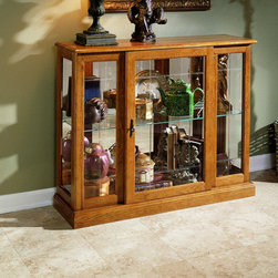 "Pulaski - Keepsakes Console Curio Cabinet - Fall in love with graceful elegance of the Keepsakes Ridgewood cherry console curio display cabinet by Pulaski Furniture. Crafted of select hardwood solids and veneers for durability and strength, this console curio display cabinet offers V - grooved front glass with an adjustable glass shelf for storage space. The lighted interior and mirrored back charmingly show off your most precious collectibles. Nothing makes a gift more appreciated than commemorating the moment with an engraved name plate. Pulaski ""Keepsakes"" curios feature an engravable brass plaque that heightens the meaning that you attach to the special treasures inside. Included is an engraving form for you to fill out and mail to the address listed upon receipt of your curio. Shortly after, you will receive a 1"" H x 3"" W brass ownership plate engraved with your message to personalize your purchase or gift. Features: . -Keepsakes collection. -Hardwood solids and veneers construction. -V - grooved front glass. -Lighted interior. -Mirrored back. -Adjustable glass shelf. - About Pulaski Furniture: Pulaski Furniture promises you a constant commitment to providing you with the satisfaction in knowing you made the right choice in home furniture. Pulaski Furniture has been hand-crafted with pride for over half a century, and their engineering standards are three times more precise than the industry standard. Features like the patented ""Herculock"" bed rail system and dovetail drawer construction are just two examples of the value placed on quality construction. Pulaski Furniture is inspected six times before leaving the plant, guaranteeing you the finest in quality, and Pulaski's own 17-step finishing process ensures that the character, beauty, and durability of the wood remains as intact as the day it was crafted."