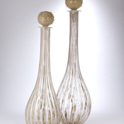 Shimmering Palace Bottle - 35 x 10.5 - Dainty and carnival-sweet but with a charming golden color used throughout, the Shimmering Palace Bottle is doubly defined by its fluted body, streaked with gold glitter throughout clear glass, and its ball stopper, which has a dandelion shape colored a rich butterscotch hue.  Use as a decanter for a rich, warm glow, or place in a window to enjoy the elite monochrome sparkle.