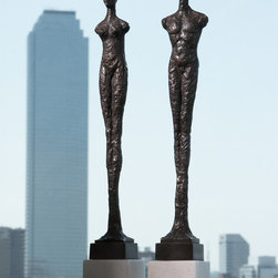 Pair of Contempo Statues - Depicting the universal human form elongated into crude, crafted architecture to unite the concepts of upward striving and earthly roots, the iconic man and woman forms of the Pair of Contempo Statues declare a binary notion that gives your transitional decor a thoughtful interplay.  Made in a bronzed black finish, the thin statues stand high on blocks of white limestone.