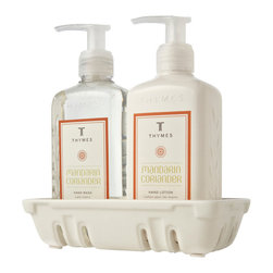 Mandarin Coriander Sink Set - Gently cleanse your hands and soften them with rich emollients with the Mandarin Coriander Sink Set of liquid hand wash and creamy hand lotion, while also enjoying the burst of happy orange scent with the brisk green-and-gold undertones of summery coriander. The two pump bottles of countertop luxury are contained by a low-profile white ceramic container inspired by berry-basket designs.
