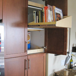 Base Cabinets and Other Creative Solutions - A sloped pull out shelf in the kitchen make the ideal place to store your cookbooks.