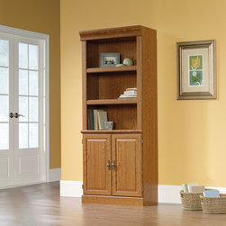 """Sauder - Orchard Hills Library Bookcase with Doors in Carolina Oak - American country style that provides endless versatility in the Orchard Hills Collection. Solid cases are softened by finely detailed moldings, raised panel doors, and brass-finished hardware, while warm Carolina Oak finish makes this piece the perfect accompaniment to the existing decor of any home. Features: -Library bookcase with doors. -Orchard hills collection. -Carolina oak finish. -Three adjustable shelves. -Hidden storage behind raised panel doors. -Enclosed back with cord access. -Patented slide on moldings. -Made in USA. -Assembly required. -Manufacturer provides 5 year warranty. -Overall Dimensions: 71.5"""" H x 29.5"""" W x 13.5"""" D."""