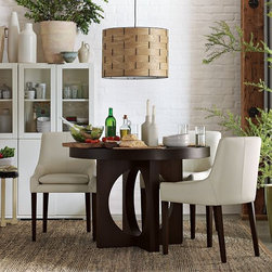 Round Dining Table with Cutout Legs - Gather 'round and 'round. Substantial yet airy, with a chunky profile and a circle-cutout base to reflect the circular top, this piece is perfect for small family meals or more romantic dinners for two.