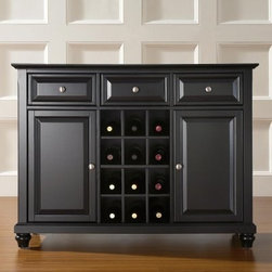 Crosley Cambridge Buffet Server with Wine Storage - Keep your favorite wines and bar accessories at your fingertips with this stunning Cambridge Buffet Server with Wine Storage. Constructed of solid hardwood and wood veneers this beautiful cabinet features raised panel doors with a hand-rubbed satin finish in a variety of shades. Two large cabinet doors open to reveal adjustable shelves and three deep drawers hold all kinds of stuff. The center section proudly displays 12 bottles of wine. Brushed metal hardware and adjustable balancing levers in the legs are quality touches. Assembles easily. Perfect for entertaining.About Crosley FurnitureIn 1920 Powel Crosley founded the company that pioneered radio broadcasting and mass market manufacturing around the world starting with a simple radio meticulously crafted with obsessive detail and accuracy and a measure of consideration for the wallet. These high ideals have served the company well for over 90 years and they live on in the newest addition to the family. Crosley Furniture sets a new standard for innovation function and meticulous craftsmanship in the manufacture of value-priced furniture. They proudly offer durable furniture products featuring hardwood and veneer construction with rich multi-step finishes in a multitude of styles.
