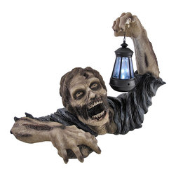 Zeckos - Dead Rising Zombie Holding Lantern Solar Powered Garden Light Lamp - Even zombies can be scared of the dark. After years spent in the cold dark ground, this emerging gruesome garden guest casts an eerie light over his shadowy surroundings with a solar powered single LED lantern. The solar lamp is powered by a single rechargeable AA battery that is charged by a solar panel circling the LED. The lamp features a simple on/off switch and a light sensor that will automatically turn the light on when the sun goes down and off when the sun comes up. The grim garden accent is made from durable cold cast resin that won't rust or deteriorate in the weather. It measures 18 1/2 inches long, 13 inches tall, and 10 1/2 inches wide. This sinister piece is a unique horror accent for your lawn, garden, or patio that will shed some light to ward off any of this zombie's unwelcome undead friends.