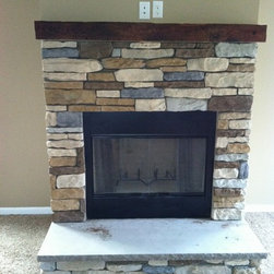 Stone Fireplace | Stone Hearth - This fireplace features a multi-color stone with a railroad tie as the mantel and a huge slab of stone for the hearth.