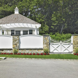 Universal Fence with Custom Gates - The convex sweep of our Freeport Universal Board fence adds charm when complementing a pillared stone wall. The impressive 6' double gate features a crisscross motif and convex spindle topper. Over the fence a Freeport attached pergola is visible.