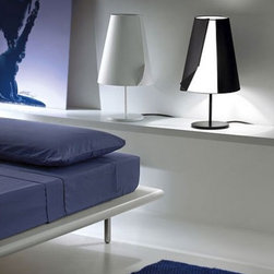 """Pallucco - Pallucco Guardian of Light table lamp - The Guardian of light table lamp from Pallucco has been designed by Susanne Phillippson in 2006. This table mounted luminaire is great for halogen lighting. The Guardian of light is constructed of a polycarbonate shade which is available in black, aluminum grey or white. Liquid rubber coated metal makes up the structure of this fixture, which is also available in a black, white or aluminum grey finish. The Guardian of Light looks like a classic lampshade until it is switched on, at which point you realize that the classical form conceals an innovative idea: the shade is a cloak that wraps around itself, keeping the magic of the light secret. When the cloak is opened, by means of the protruding flap, the lamp gently releases its light, which goes out again when the cloak is closed. The lamp has a """"soft start"""" feature so that it can be switched on and off automatically when the shade is opened and closed. The Guardian of Light table lamp exhibits a sophsticated and innovative design, along with quality craftsmanship, that is sure to brilliantly illuminate any modern atmosphere.  Product Details:  The Guardian of light table lamp from Pallucco has been designed by Susanne Phillippson in 2006. This table mounted luminaire is great for halogen lighting. The Guardian of light is constructed of a polycarbonate shade which is available in black, aluminum grey or white. Liquid rubber coated metal makes up the structure of this fixture, which is also available in a black, white or aluminum grey finish. The Guardian of Light looks like a classic lampshade until it is switched on, at which point you realize that the classical form conceals an innovative idea: the shade is a cloak that wraps around itself, keeping the magic of the light secret. When the cloak is opened, by means of the protruding flap, the lamp gently releases its light, which goes out again when the cloak is closed. The lamp has a """"soft start"""" feature so that i"""