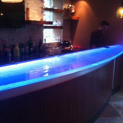 "Glass counter top with LED - Thermoformed glass bar top, 2"" thick.  starphire over pattern.  Glass has been backlit using LED lighting with Traxon control for ""millions of colors"". Private residence. Photo is shown during installation"