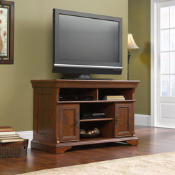 """Sauder - Arbor Gate 42"""" TV Stand - Traditional motifs meet modern function in the Arbor Gate collection. Skillfully designed layers of beautiful detailing include panel doors with beaded frames, large crown moldings over plinth buttressing, frame and panel construction elements and contoured foundations. The thoughtful design and attention to detail extend to functional updates that incorporate contemporary technology solutions for flat panel televisions, computer monitors and laptop computers. The deep color and rich grain of Coach Cherry finish, combined with authentic pulls in an old-brass finish, carry a timeless patina that allows Arbor Gate to effortlessly blend tradition and technology into an ideal solution for modern day living. Features: -Holds TVs weighing up to 95 lbs or less; base must not be longer than 42 inches.-Divided shelving provides dedicated storage for audio/video components.-Adjustable center shelf.-Storage area behind doors features an adjustable shelf and holds VHS tapes, CDs and DVDs.-Coach Cherry finish.-Accented with solid wood feet an detailing.-Arbor Gate collection.-Recommended TV Type: Flat.-TV Size Accommodated: 42"""".-Finish: Coach Cherry.-Powder Coated Finish: No.-Gloss Finish: No.-Material: Engineered wood.-Solid Wood Construction: No.-Distressed: No.-Exterior Shelves: Yes.-Drawers: No.-Cabinets: Yes -Number of Cabinets: 2.-Number of Doors: 2.-Door Attachment Detail: Hinges.-Interchangeable Panels: No.-Magnetic Door Catches: Yes.-Cabinet Handle Design: Knobs..-Scratch Resistant: No.-Removable Back Panel: No.-Hardware Finish: Dark brown metal.-Casters: No.-Accommodates Fireplace: No.-Lighted: No.-Media Player Storage: Yes.-Media Storage: Yes.-Cable Management: Cable hole.-Remote Control Included: No.-Weight Capacity: 95 lbs.-Swatch Available: Yes.-Commercial Use: No.-Collection: Arbor Gate.-Eco-Friendly: Yes.-Recycled Content: No.-Lift Mechanism: No.-Expandable: No.-TV Swivel Base: No.-Integrated Flat Screen Mount: No.-Non-Toxic: Ye"""