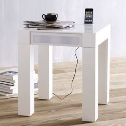 Parsons Audio End Table - The introduction of the iPhone has brought clutter into our bedrooms. Millions of these devices spend the night sitting on an end table next to a bed, either playing or plugged into some garish charging station. The iPhone itself has replaced the old clock radio as the device that plays music as we drift to sleep and wakes us up with an alarm. Still, many use audio charging stations to amplify the iPhone's sound. The $319 Parsons Audio End Table eliminates the need for the charging station, external speakers and audio cables. The table itself has an electrical cable to power the speakers and charge the phone. Made from engineered wood with a white lacquer finish, it conceals speakers and cables inside. The top is broken only by a small place to insert the iPhone. Once plugged in, the phone charges, and any audio coming from the phone is played through the table's speakers.